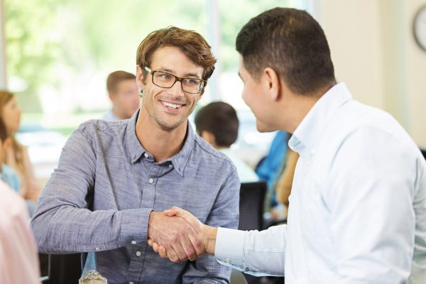 Mid adult Caucasian and Hispanic businessmen shake hands during meeting. They are attending a breakout session during a seminar.