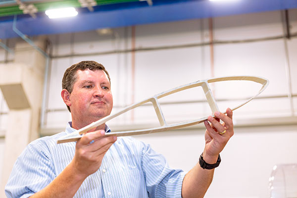 Image of Dr. Todd Griffith holding prototype turbine blade.